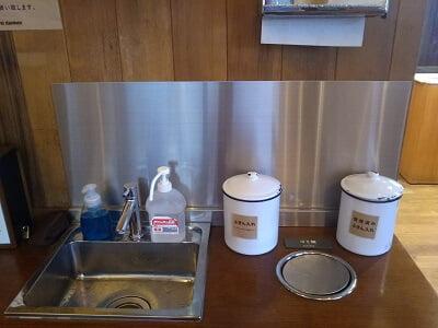 ダンケン谷山店のイートインスペースの手洗い場とふきんとごみ入れの写真